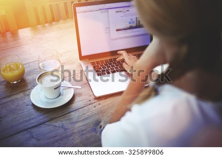 Cropped shot view of a women's hands keyboarding on laptop, young female person working on net-book while sitting in coffee shop indoors, blonde female freelancer connecting to internet via computer  - stock photo