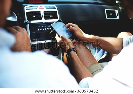 Cropped shot view of a young man using navigation on mobile phone while sitting on front seat in luxury car cabriolet, male viewing location map in network via cell telephone during road trip  - stock photo