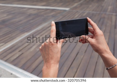 Cropped shot view of woman's hands holding cell telephone with copy space area for your text message or advertising content, female photographing urban view with mobile phone camera during walking  - stock photo