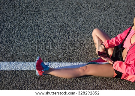 Cropped shot view of young female runner using mobile phone while sitting on a road with copy space background for your text or content, fit woman using cell telephone while resting after training  - stock photo