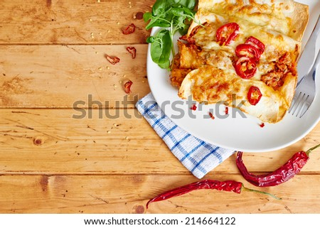 Cropped top view showing enchiladas dish with chili peppers on a wooden table, with space - stock photo