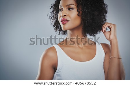 Cropped upper body view of beautiful young African woman looking sideways with hands touching hair and copy space - stock photo