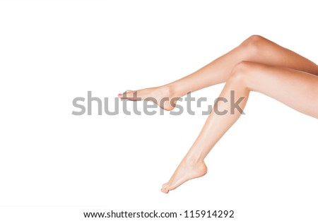 Cropped view image of a beautiful pair of sexy legs with bare feet extending into the frame from the right on a white background - stock photo