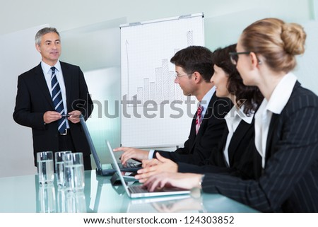 Cropped view image of a row of businesspeople working on laptops and tablets during a presentation or meeting
