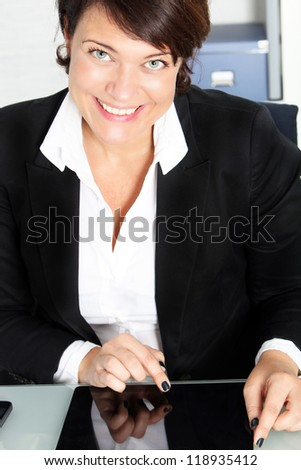 Cropped view image of a smiling businesswoman sitting at her desk using a touchscreen modern tablet - stock photo