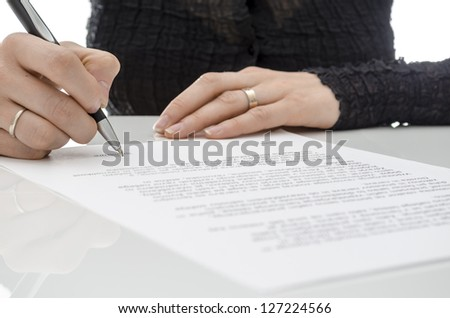 Cropped view of a business woman signing a contract above signature line. - stock photo