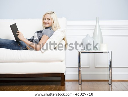 Cropped view of a woman relaxing on a white couch with a book and smiling at the camera. Horizontal format.