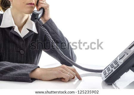 Cropped view of a woman sitting at office desk and using a phone. - stock photo