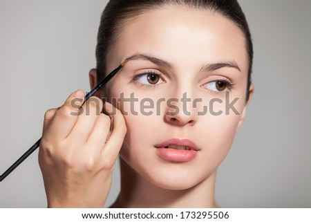 Cropped view of a young woman having brow color added to her eyebrows - stock photo