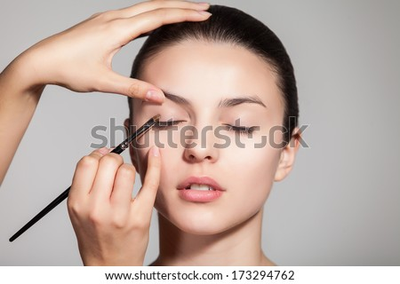 Cropped view of a young woman having eyeshadow added to her eyelids - stock photo