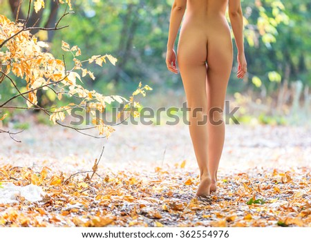 Cropped view of beautiful naked woman walking in fall forest - stock photo