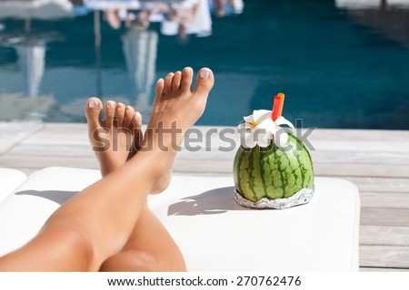 Cropped view of beautiful woman legs near swimming pool. Girl at travel spa resort pool. Summer luxury vacation. - stock photo