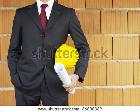 Cropped view of caucasian architect standing near red bricks with hand in pocket and blueprints. Horizontal shape, front view, copy space - stock photo