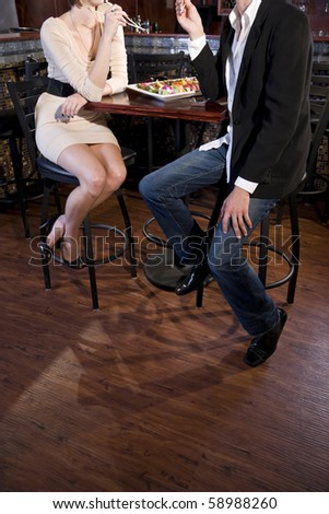 Cropped view of couple eating sushi in Japanese restaurant - stock photo