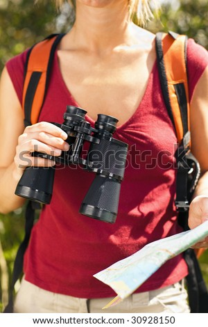 cropped view of female bird watcher holding binoculars and map. - stock photo