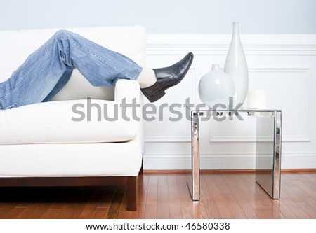 Cropped view of man reclining on white couch next to an end table holding vases, with only his legs visible. Horizontal format. - stock photo