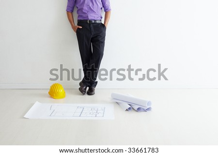 cropped view of mid adult architect leaning on wall and blueprints on floor. Copy space - stock photo