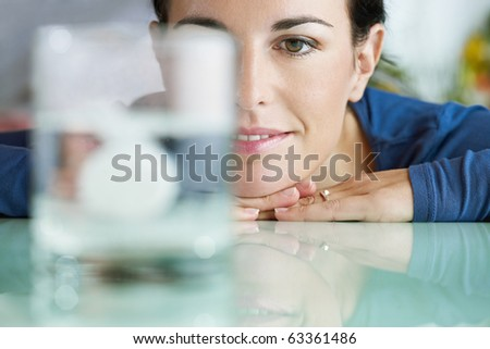 cropped view of mid adult woman leaning on table and looking at effervescent tablet dissolving in water. Horizontal shape, front view, copy space - stock photo