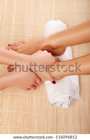 Cropped view of the hands of a female beautician giving a foot massage treatment in a spa or resort - stock photo