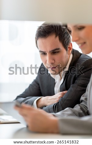 Cropped view of two work colleagues, a young man and woman, analyzing information or a report on a tablet computer as they sit together at office desk working. - stock photo