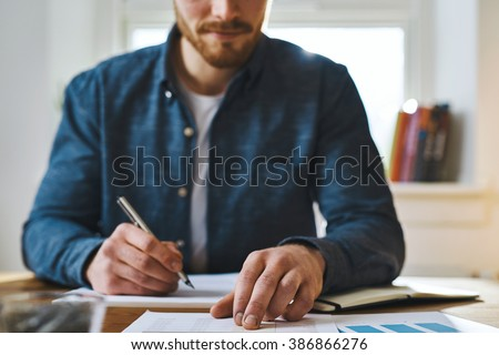 Cropped view of unidentifiable man in blue shirt with hand over paperwork as if to check statistics or plan something important
