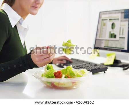 cropped view of woman eating salad in office. Copy space - stock photo