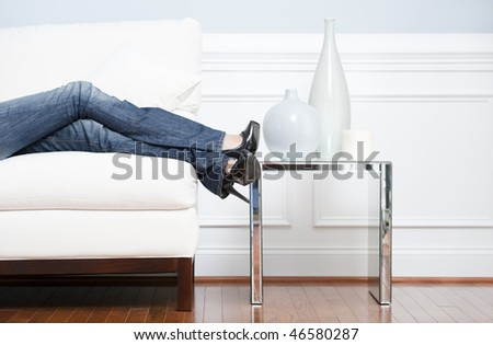 Cropped view of woman reclining on white couch next to an end table holding vases, with only her legs visible. Horizontal format. - stock photo
