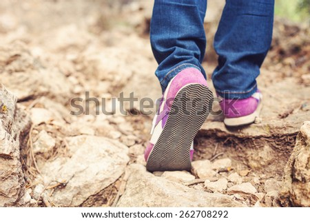 Cropped view of woman walking along trail in mountains - stock photo