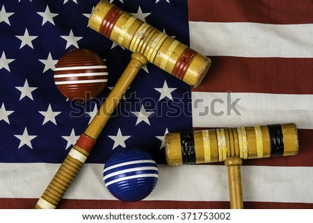 croquet mallets and balls on American flag - stock photo