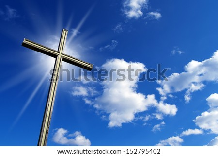 Cross Against the Blue Sky / Wooden high cross with blue sky, clouds and reflection - stock photo