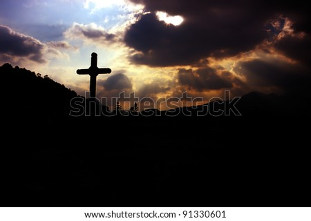 cross and god rays on the cloudy sky - stock photo