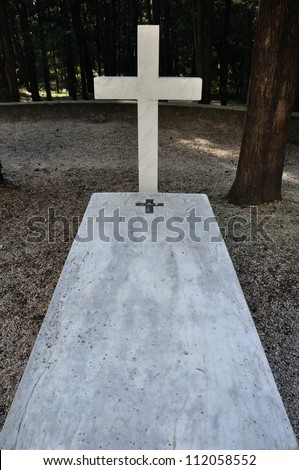 Cross and marble grave tombstone among trees. - stock photo
