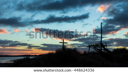 Cross and shelter frame with the sun dawns in the background.