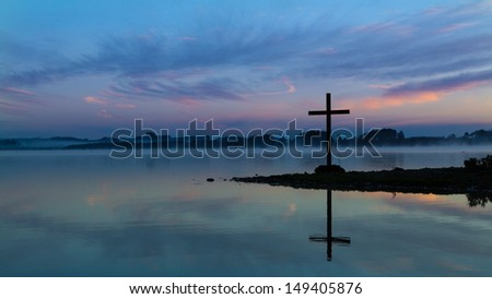 Cross at a lake with wonderful morning sky colors.