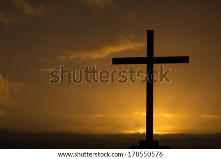 Cross at dawn with the sun behind the cross. - stock photo