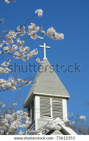Cross atop a rural church seen from behind cherry blossoms.