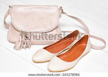 cross-body handbag and shoes on a white background  - stock photo