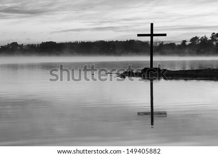 Cross by a lake waters with some background mist.
