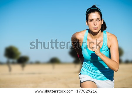Cross country running sweaty woman. Female runner on countryside training. - stock photo