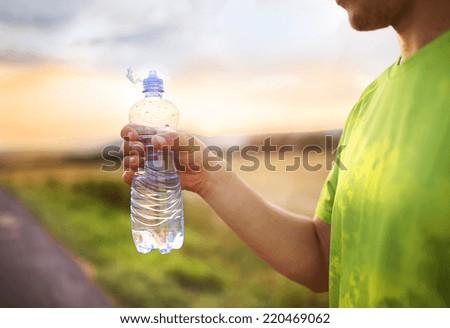 Cross-country trail running man having water break at sunset - stock photo