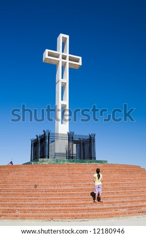 Cross dedicated to veterans of American wars on top of Mount Soledad in La Jolla California. Girl showing respect for those that have served in the armed forces. - stock photo