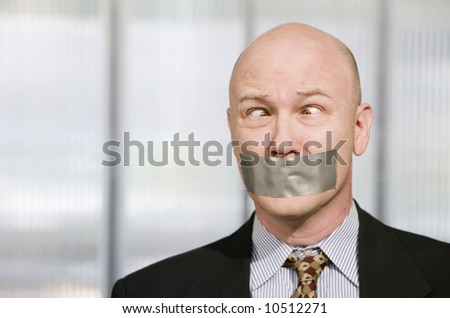 Cross-eyed businessman silenced with duct tape over his mouth - stock photo