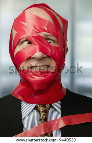 Cross-eyed businessman wrapped in red tape - stock photo