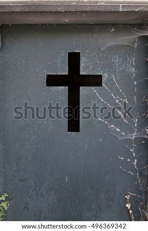 Cross in a door of a cemetery, a grim picture