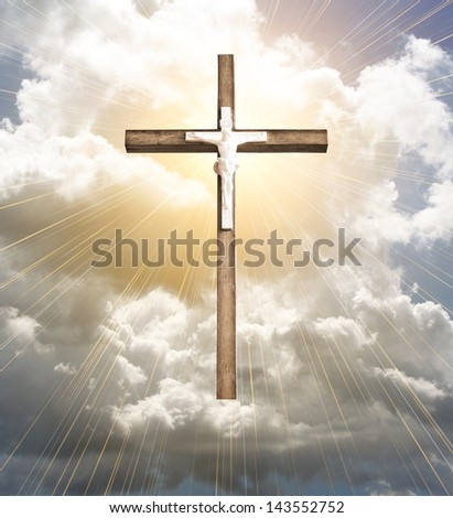 cross in sun rays against cloudy sky