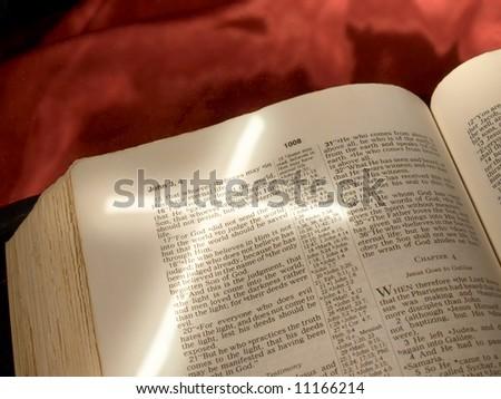 Cross light shape angled across Bible page open to John 3:16 - stock photo