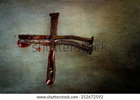 Cross of nails with blood puddled on ends and sprinkling around edges with room for text. - stock photo