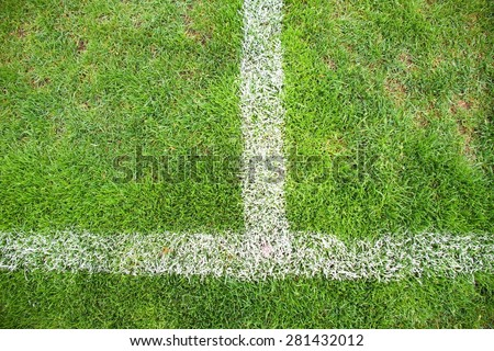 Cross of painted white lines on poor natural football grass. Artificial green turf texture.  - stock photo