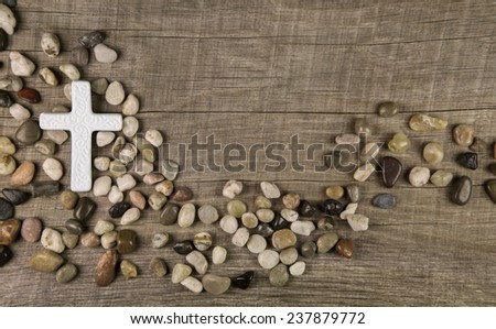 Cross of stones on wooden background for condolence or mourning cards. - stock photo