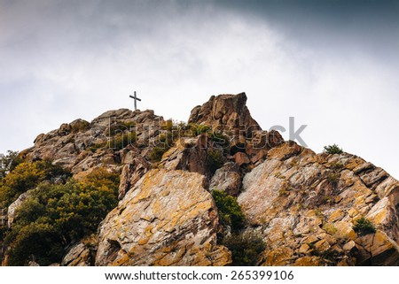 Cross on a stone mountain, Christian symbol - stock photo